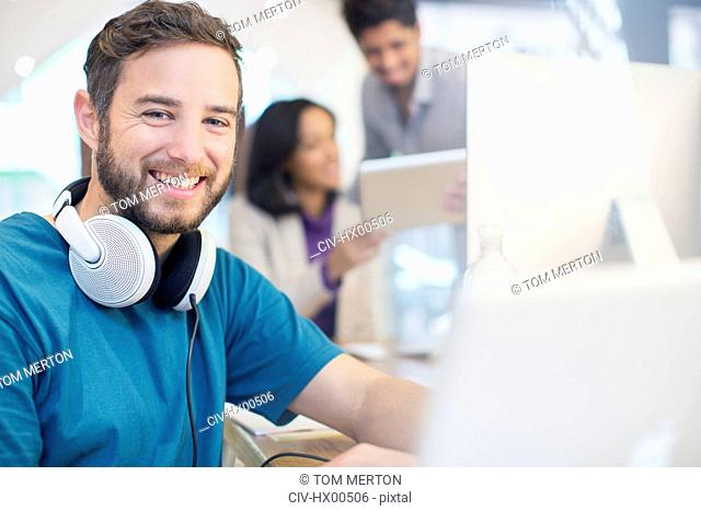 Portrait confident creative businessman with headphones working in office