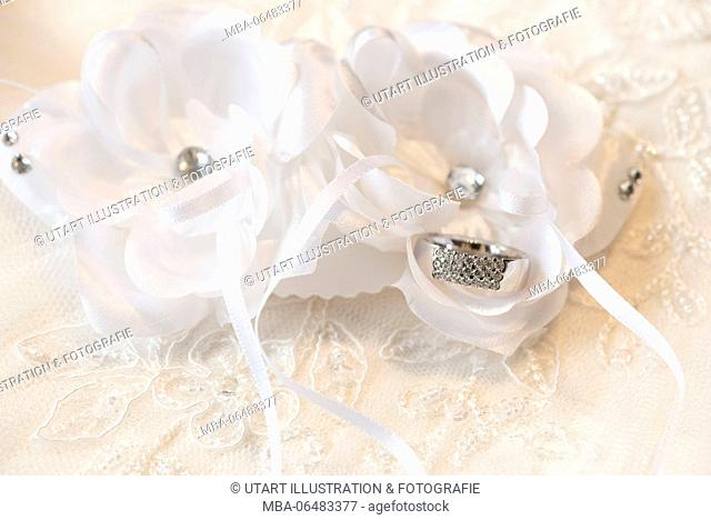 Ring made of platinum with diamonds in front of white textile flowers on a background made of lacy
