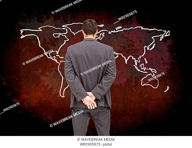 Businessman looking at Colorful Map with paint splatters on wall background