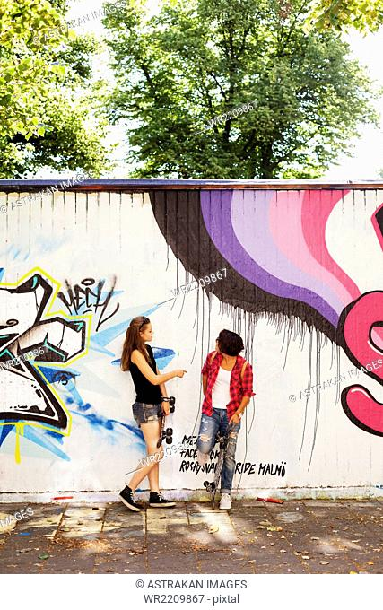 Girls standing on footpath against wall with graffiti