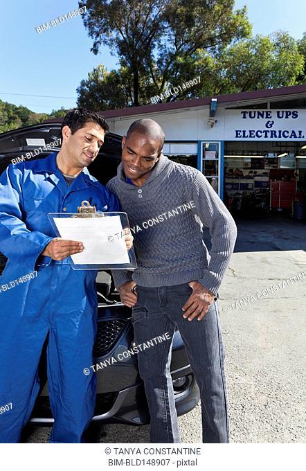 Mechanic explaining paperwork to customer