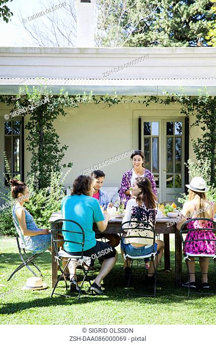 Friends leisurely enjoying meal together outdoors