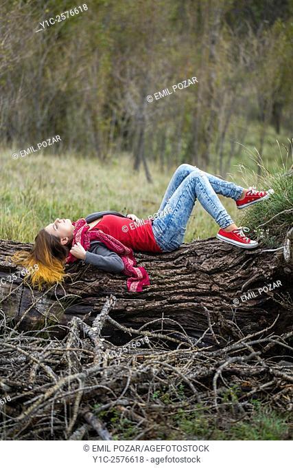 Teen girl in denim pants and sneakers in nature across fallen tree