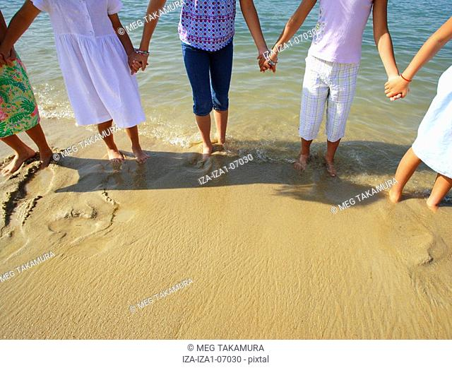 Low section view of five girls standing on the beach and holding each other's hands