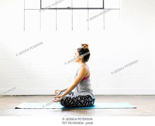 Woman meditating on exercise mat