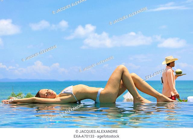 woman lying at the surface of a swimming pool, relaxing