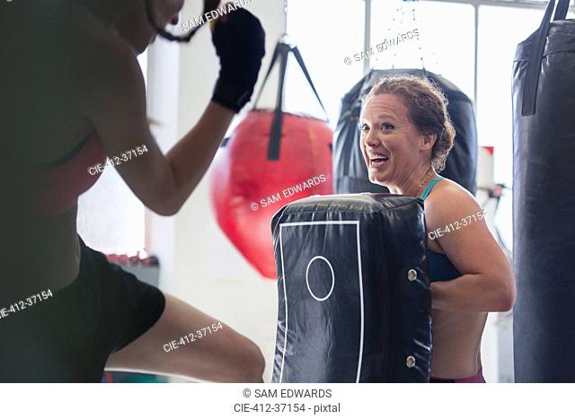 Smiling female boxers kickboxing with padding in gym