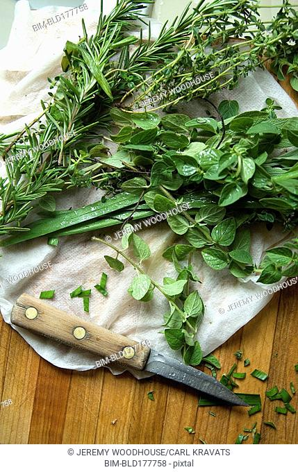 Knife with fresh herb leaves