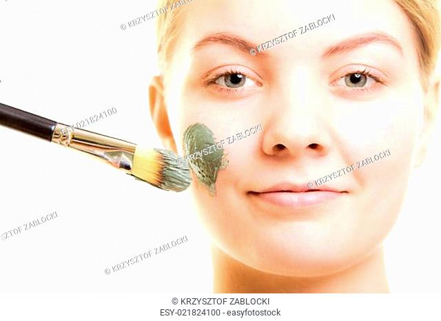 Skin care. Woman applying clay mud mask on face