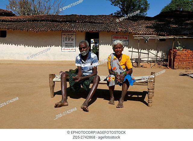 Old couple sitting on a Cot, ORAON TRIBE, Purkela Village, Taluka Lundra, District Sarguja, Chattisgarh, India