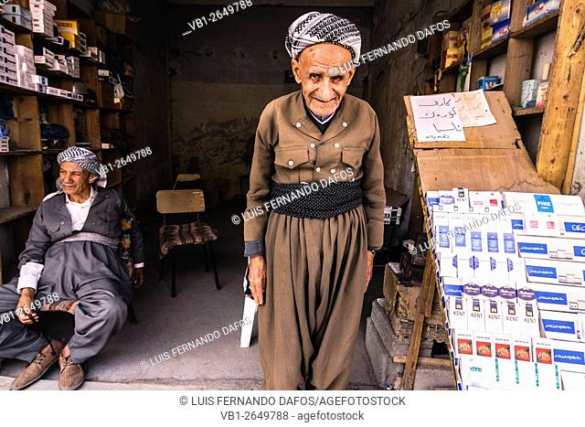 Two old Kurdish men in traditional dress at a shop in Erbil, Iraq
