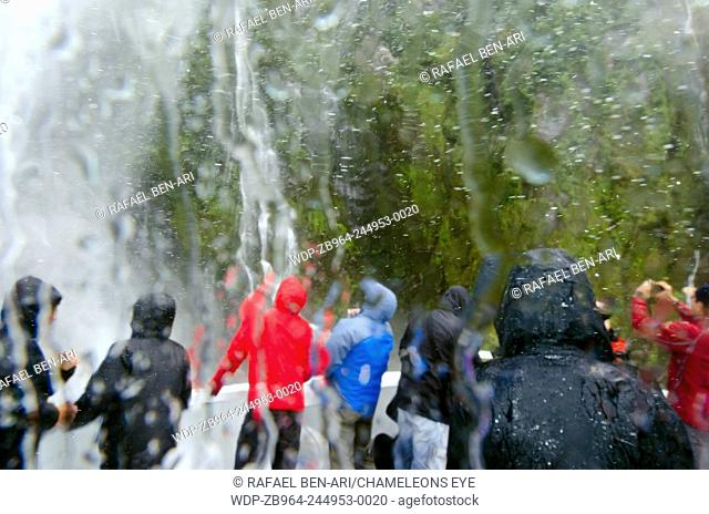 MILFORD SOUND,NZ - JAN 14:Visitors under waterfall in Milford Sound on Jan 14 2014.It has been judged the world's top travel destination in the 2008 Travelers...