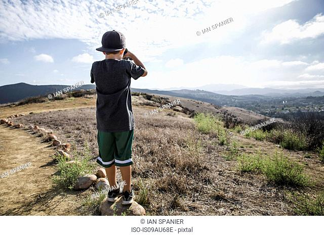 Rear view of boy looking through binoculars from footpath stone, Thousand Oaks, California USA