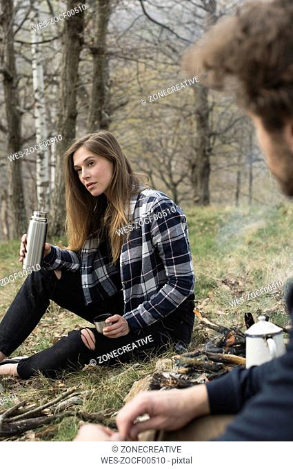 Woman with thermos flask at campfire in forest