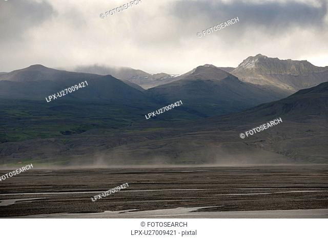 Grey cloud landscape of mountain range and meadow