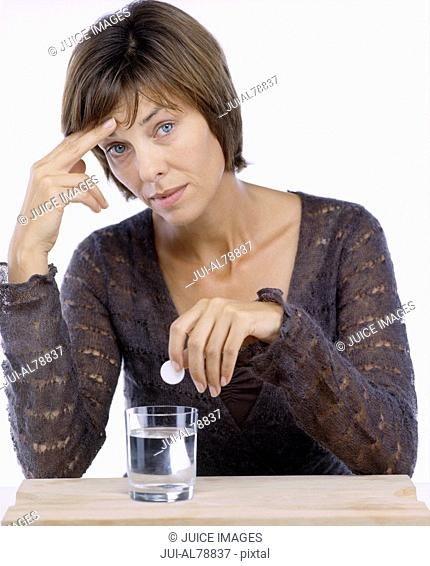 Studio shot of woman dropping effervescent medicine in glass of water