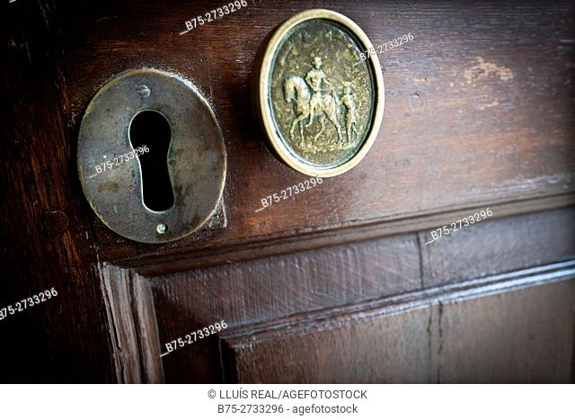 Antique door lock with ornament on hardwood door. St Martin-in-the-Fields, Trafalgar Square, London, England