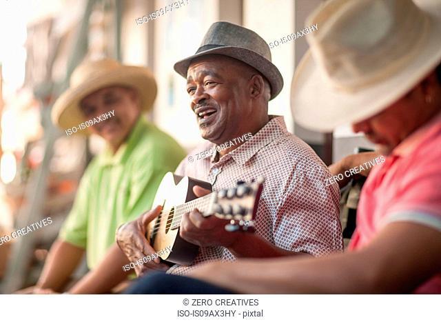 Man playing ukulele, entertaining friends