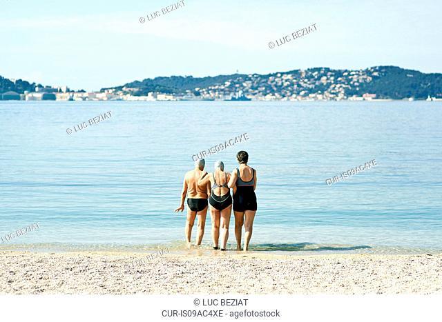 Three senior friends walking into the sea, rear view