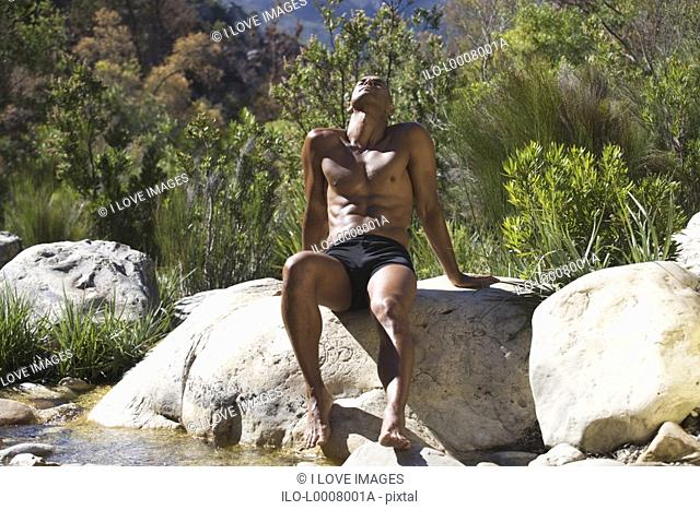 Young athletic man sitting in a natural setting