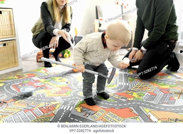 baby toddler child next to parents in children's room, holding golf ball, standing on child's game carpet with printed streets, in Cottbus, Brandenburg, Germany