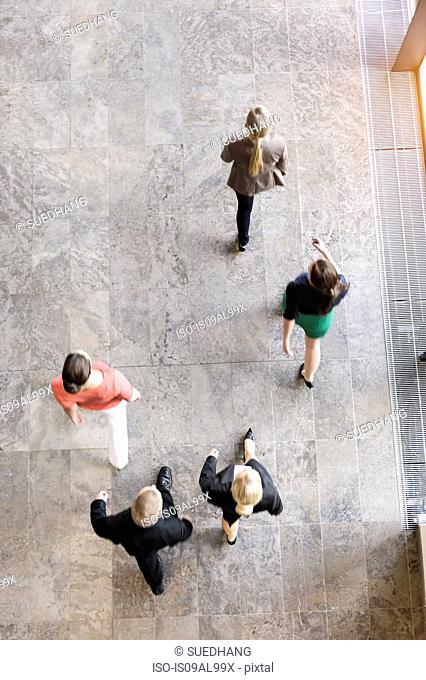 Overhead view of businesswomen and man walking in same direction