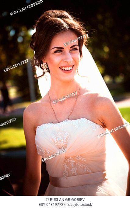 The beautiful brunette bride on a walk in park