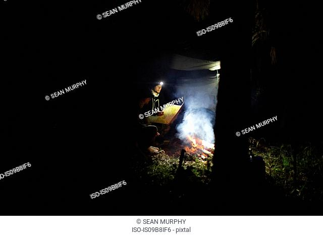 Two men sitting by campfire, looking at map