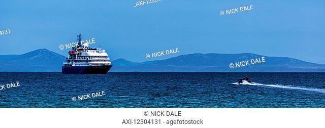 Zodiac heads towards cruise ship in sunshine; Antarctica