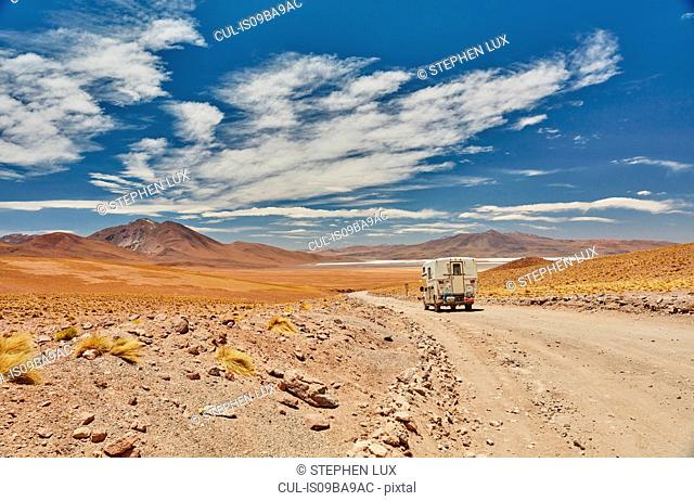 Recreational vehicle moving across landscape, rear view, Chalviri, Oruro, Bolivia, South America