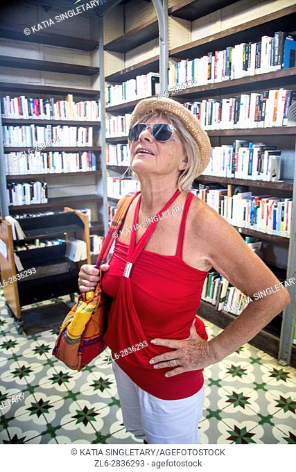 The famous national library of Fort de France in Martinique. Caucasian retired blond Woman with red top and straw hat, looking all the books and exhibit in the...