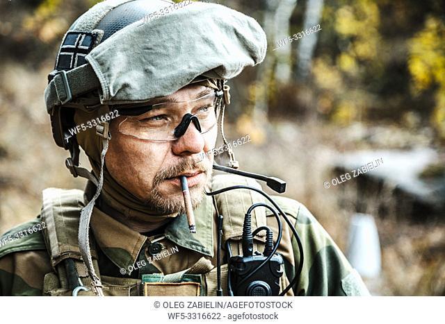 Norwegian Armed Forces Special Command FSK soldier smoking cigarette closeup portrait. Radio and headset are on