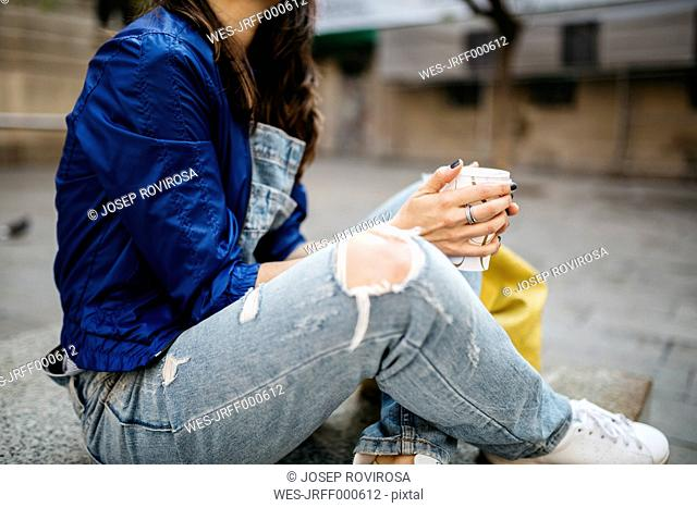 Young woman with a coffee in the city