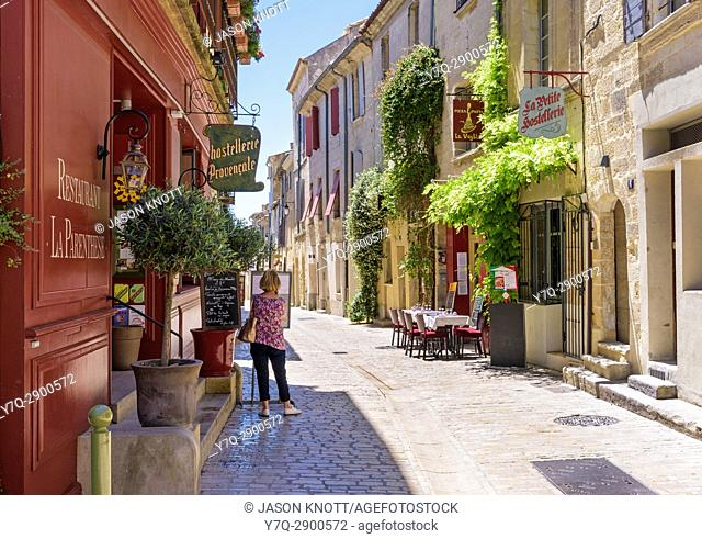 Woman looking at a restaurant menu in a picturesque street within the medieval town of Uzès, Nîmes, Gard, Occitanie, France