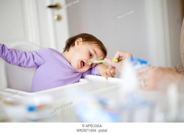 Mother feeding daughter with spoon at home