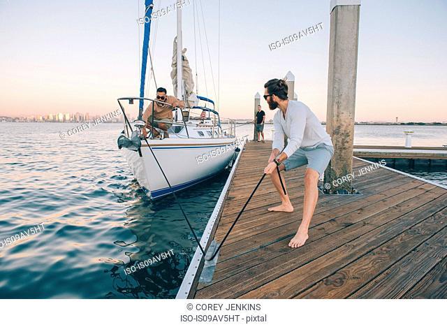Man preparing sailboat, San Diego Bay, California, USA