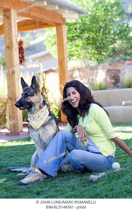 Hispanic woman playing with dog in backyard