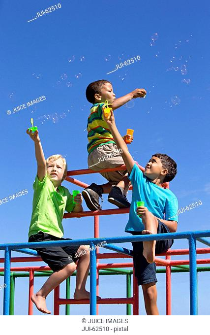 Boys blowing bubbles with bubble wands on playground