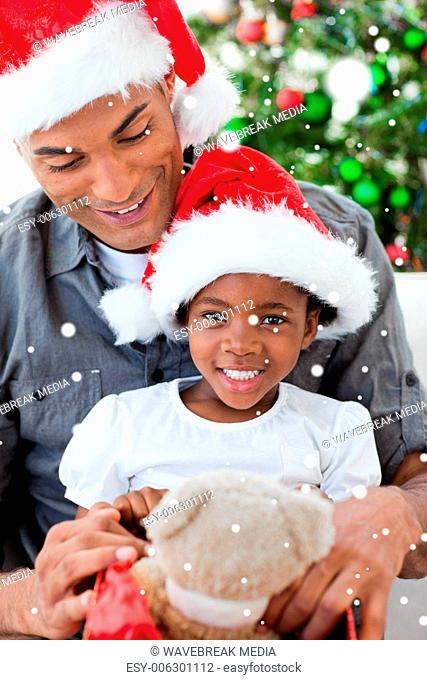Composite image of happy little girl playing with a christmas gift with her father