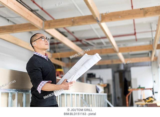 Korean architect holding blueprints and examining ceiling