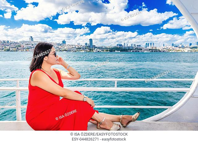 Beautiful Chinese woman cruises in ferry with view of Istanbul Bosphorus in Turkey
