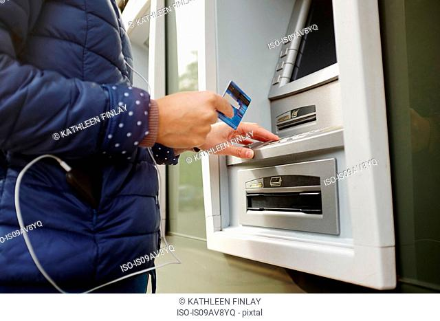 Young woman using cash machine, mid section