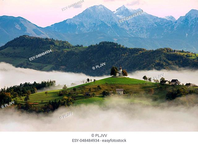 The church of St. Thomas (Sveti Tomaz) on a hilltop in the Slovenian countryside near Skofja Loka surrounded with fog with in the background snow on the peaks...