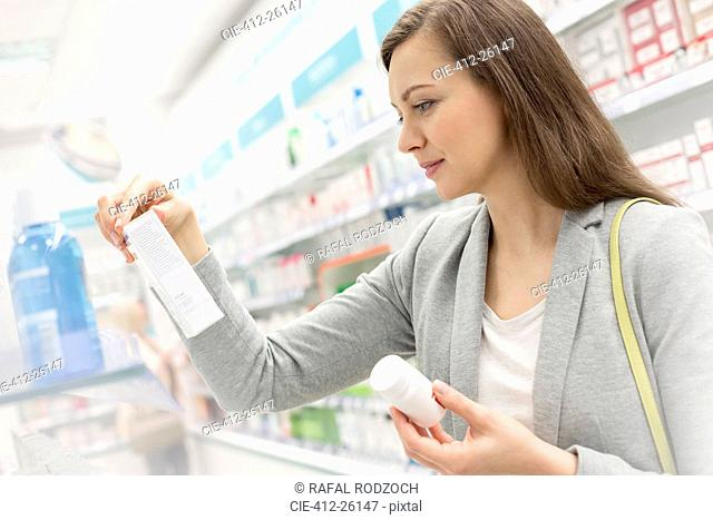 Customer reading label on box in pharmacy