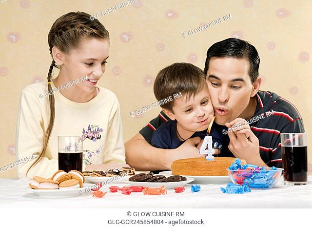 Man blowing out birthday candle with his son and daughter