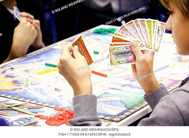 Visitors play games at the 35th International Game Days expo in Essen, Germany, 26 October 2017. Around 1100 exhibitors are displaying their wares at the show