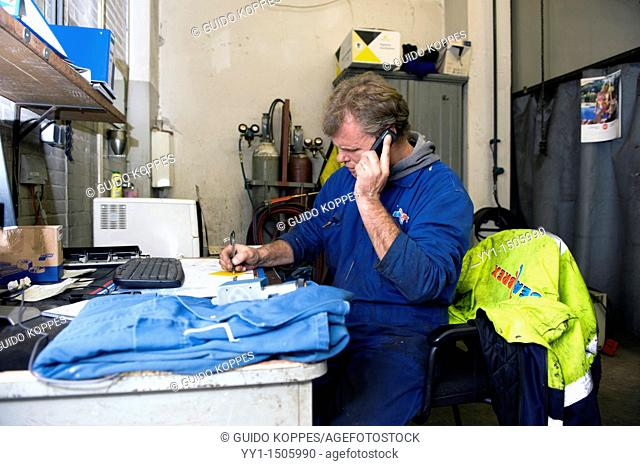 Rotterdam, Netherlands. Mid adult technical specialist and blue collar worker inside his harbour warehouse workshop