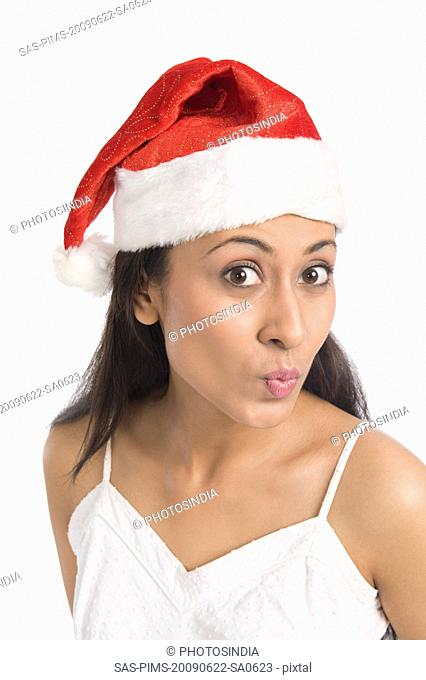 Close-up of a woman wearing a Santa hat and puckering