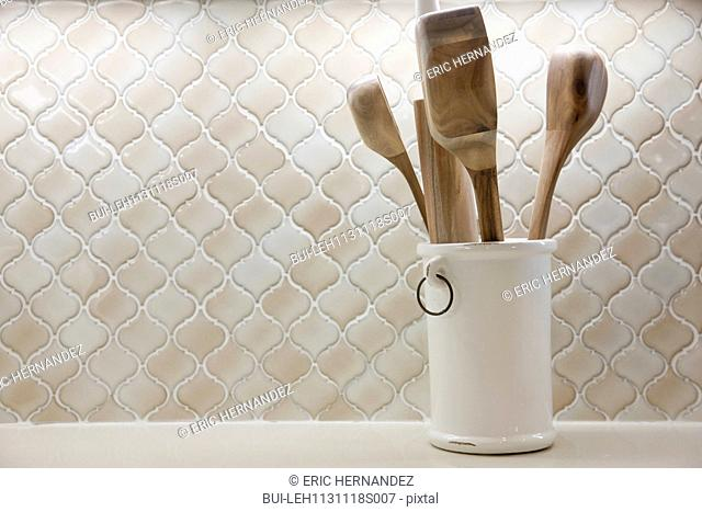 Close-up of wooden spoons in holder on shelf at home; Irvine; California; USA
