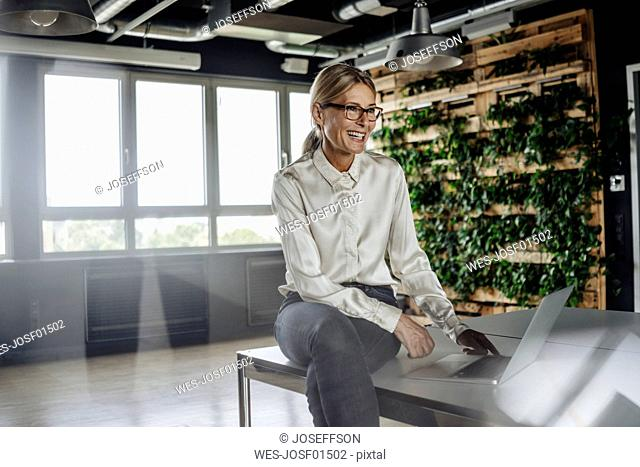 Happy businesswoman in office using laptop